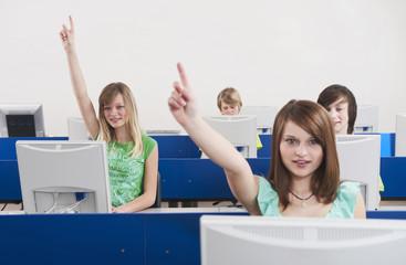 Deutschland,Emmering,Mädchen (12-13) Hand erhoben mit Studenten im Hintergrund,lächelnd