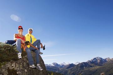 Zwei Frauen, die in den Bergen, auf Felsen sitzt