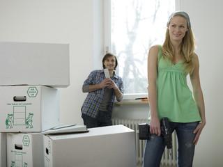 Frau mit Bohrmaschine,Mann stützte sich auf Fensterbank im Hintergrund