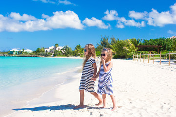 Little adorable girls on white beach walking by the sea