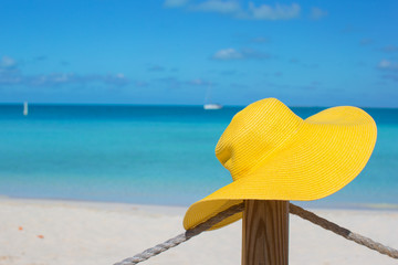 Yellow hat on the fence at tropical white beach