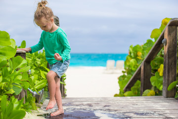 Little cute girl washes out the sand from her feet on tropical