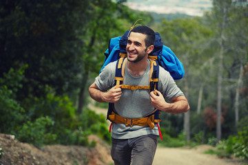 Young hiker with rucksack walking up on the trail and smiling