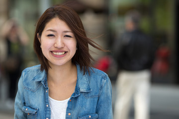 Young Asian woman in a city smile happy face portrait