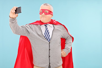 Mature man in superhero costume taking selfie