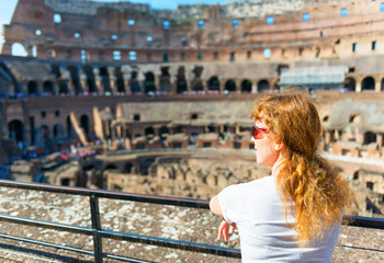 Young female redhead tourist looks at the Colosseum in Rome