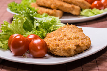 Fried battered chicken breast fillet  with lettuce on the plate