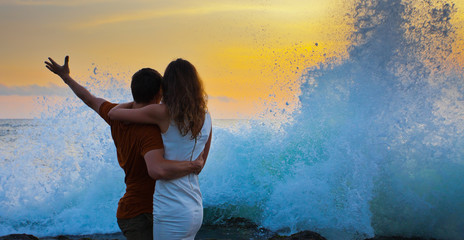 young embracing couple standing on the beach, with a wave
