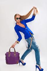 Модная девушка в джинсах и с сумкой