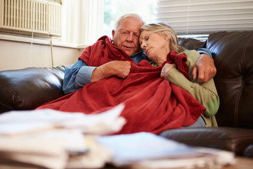 Senior Couple Trying To Keep Warm Under Blanket At Home Fototapete