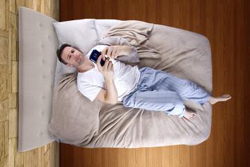 man snoozing modern cell phone alarm clock