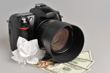 Photo camera, wedding boutonniere, rings with money on gray