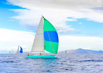 Sailing boat with a green blue spinnaker Poros island Greece