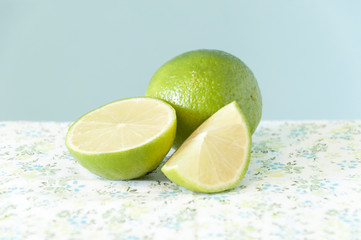 Two fresh green limes on a table with a flowered tablecloth