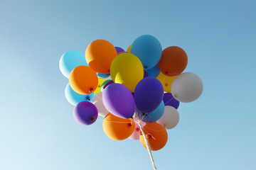 A multicolored balloon bunch in a blue sky