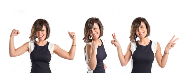 Pretty woman making the victory gesture over white background