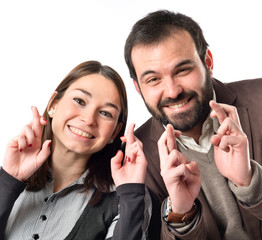 Couple with their fingers crossing over white background