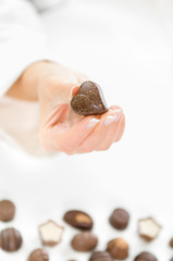 Women chef holding heart shaped Chocolate candy