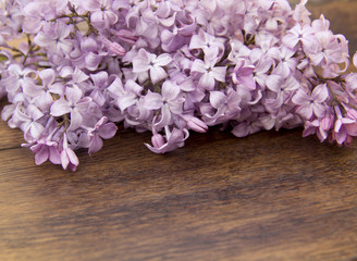sprig of lilac lies on a wooden surface