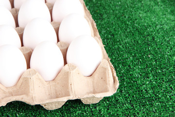 Eggs in paper tray on grass close-up