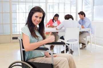 Attractive businesswoman in wheelchair gives thumbs up to camera