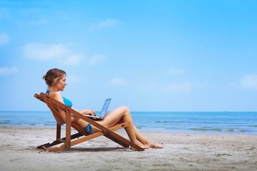 woman in bikini sitting with laptop on the beach