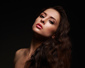 Beautiful makeup woman with long curly hair on black background
