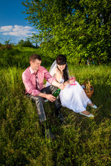 groom opens champagne at picnic in park
