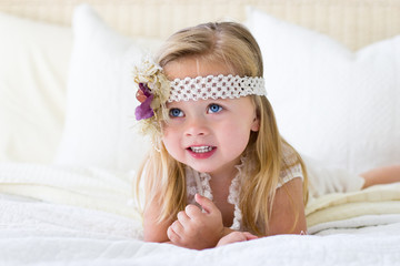 Little girl with headband on bed