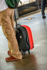man wait train (BTS) with him baggage red and rucksack