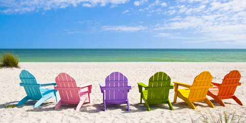 Deurstickers Strand Adirondack Beach Chairs on a Sun Beach in front of a Holiday Vac