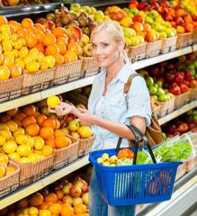 Girl at the shop choosing fruits and vegetables hands lemon