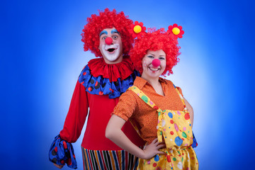 Clown couple in costumes on blue background