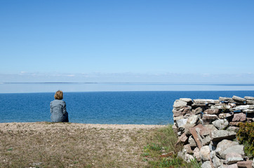 Woman sitting by the coast looking at clear blue sky and water