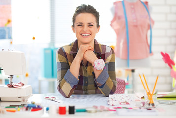 Portrait of smiling seamstress in studio