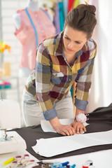 Seamstress making pattern on fabric