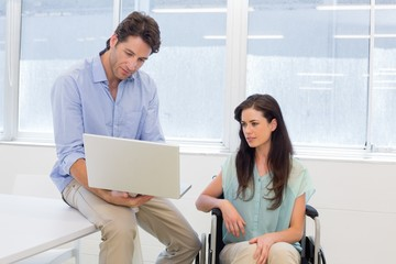 Businessman showing woman in wheelchair the laptop