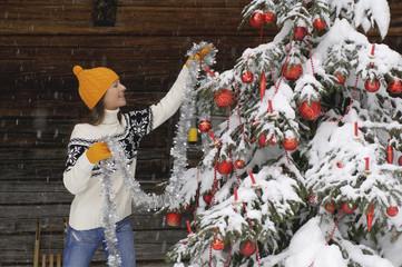 Junge Frau schmückt Weihnachtsbaum im Schnee, lächelnd