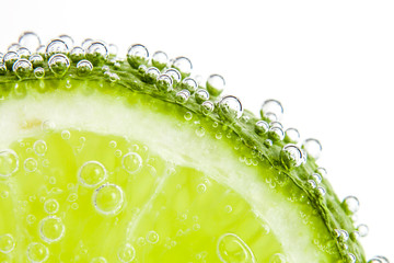 slice of  lime in the water with bubbles