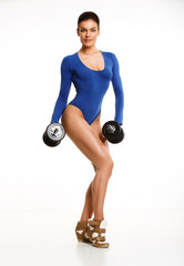Woman bodybuilder in blue body, posing in the studio with dumbbe