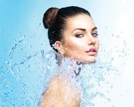 Beautiful girl under splash of water over blue background