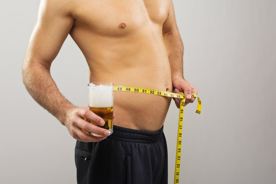 Man with glass of beer and tape measure