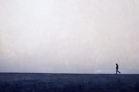 man walking  alone on the horizon line