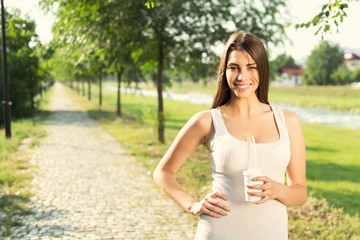 Young woman in park with takeaway coffee