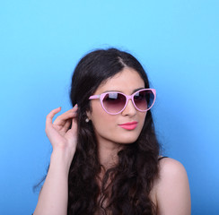 Portrait of woman with retro glasses against blue background
