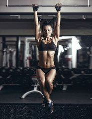 sexy young fitness brunette woman pulls up in the gym.
