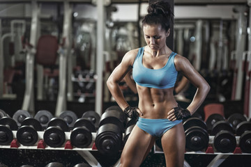 Fitness woman in sport wear with perfect body resting in gym