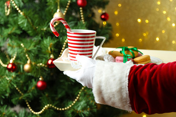 Santa holding mug and plate with cookies in his hand,