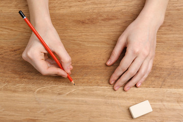 Human hands with pencil and erase rubber