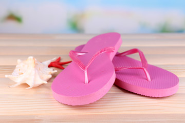 Bright flip-flops on wooden table, on nature background